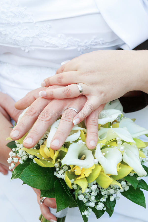 Bride and groom's hands with wedding rings stock photography