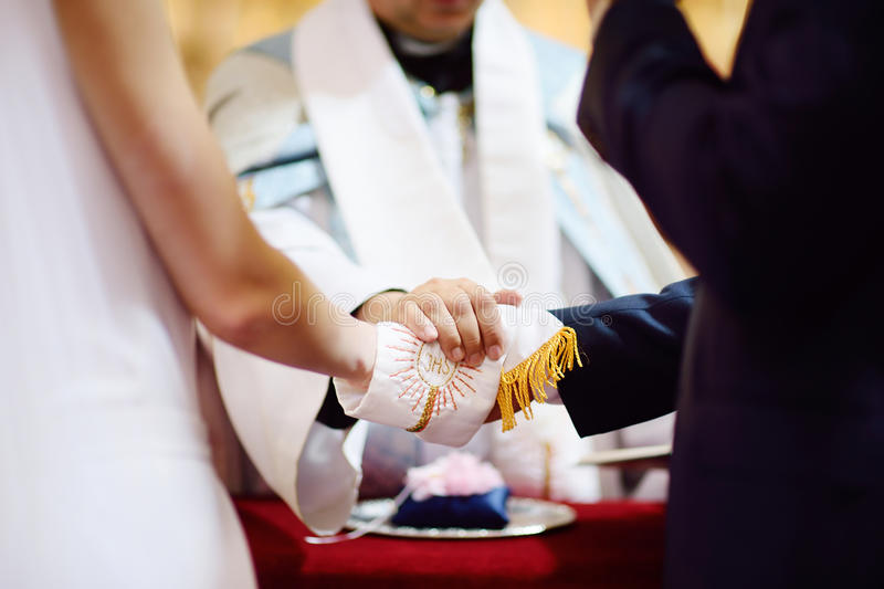 Bride and groom's hands wrapped in priest's cassock. Catholic wedding: bride and groom's hands wrapped in priest's cassock stock photo