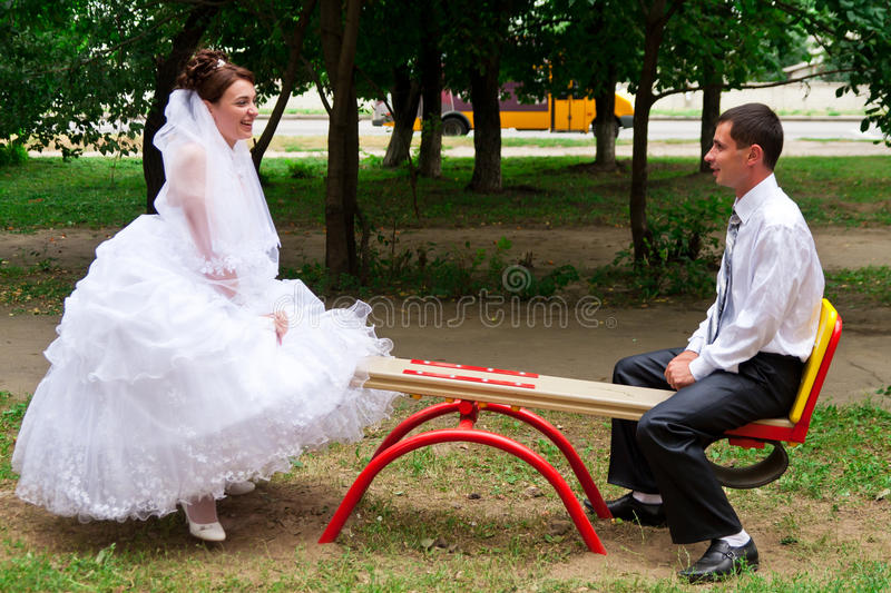 Bride and groom on a seesaw. On children's playground royalty free stock photo