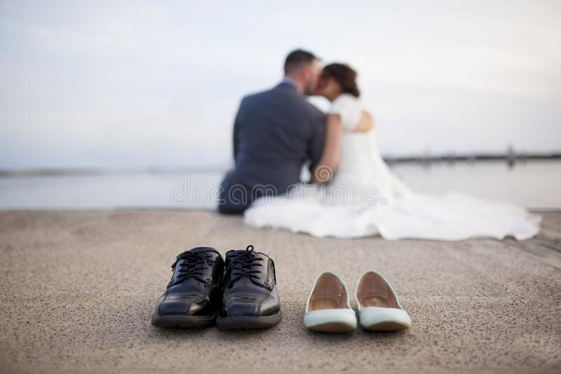 Bride and groom shoes with couple out of focus kissing in background royalty free stock photo