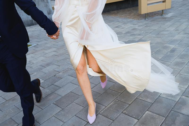 The bride and groom are on the sidewalk, legs close-up royalty free stock photography