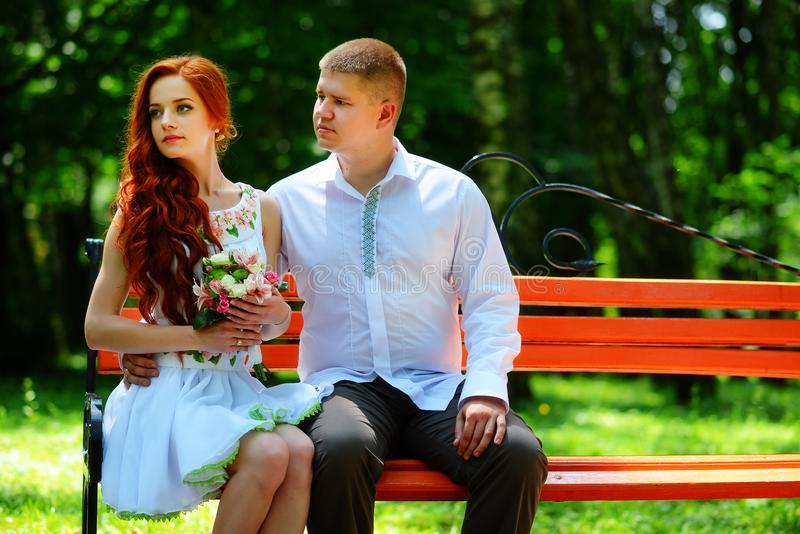 The bride and groom sit on a bench royalty free stock photos