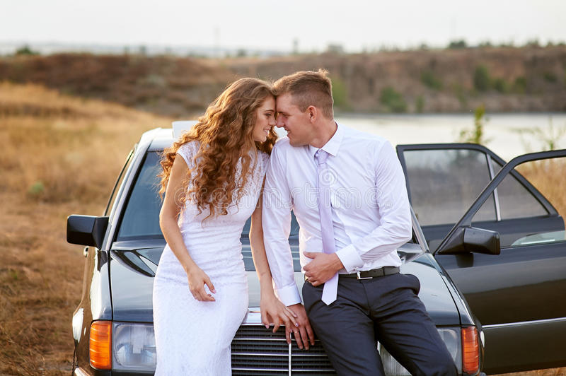 Bride and groom sit on the hood of the car stock photo