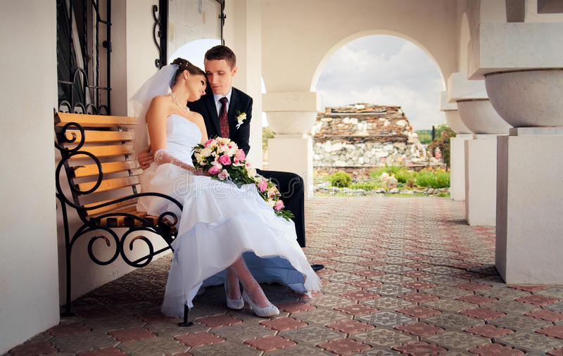 The bride and groom sitting on a bench royalty free stock images