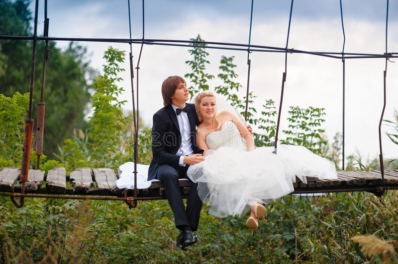 Bride and groom sitting on a bridge royalty free stock images