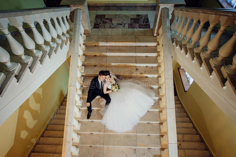 The bride and groom are sitting on a white marble staircase, holding hands and looking in the same direction stock photos