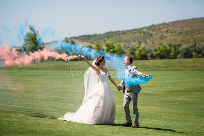 The bride and groom with smoke bombs on a field with green grass. Newlyweds walking outdoors at wedding day. Girl in. Luxury long white dress and men in stock images
