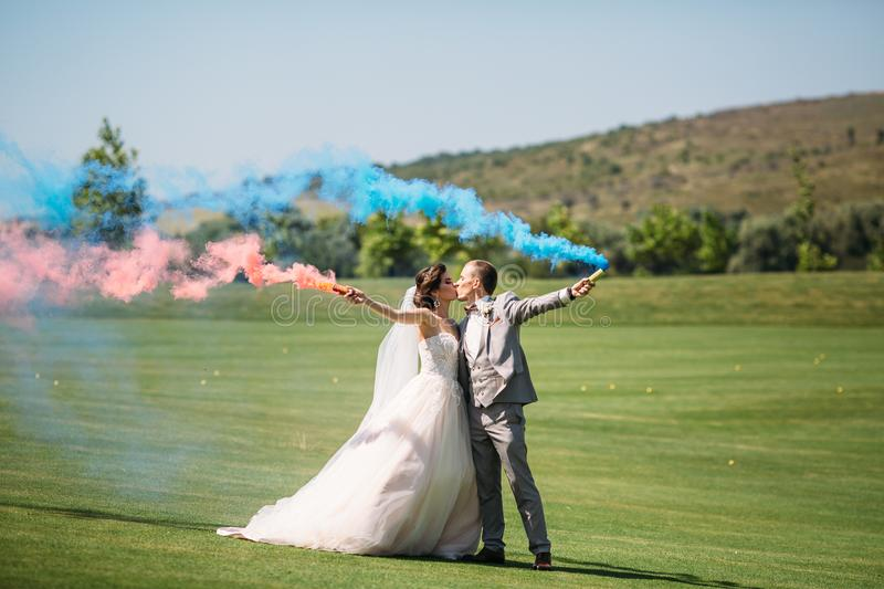 The bride and groom with smoke bombs on a field with green grass. Newlyweds walking outdoors at wedding day. Girl in. Luxury long white dress and men in royalty free stock photography