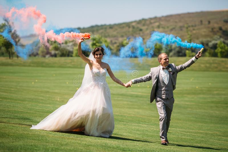 The bride and groom with smoke bombs on a field with green grass. Newlyweds walking outdoors at wedding day. Girl in. Luxury long white dress and men in royalty free stock photos