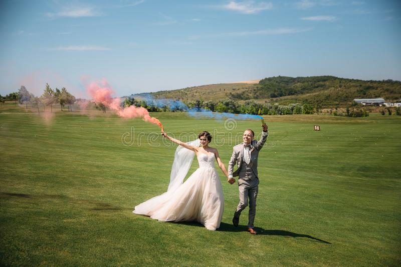 The bride and groom with smoke bombs on a field with green grass. Newlyweds walking outdoors at wedding day. Girl in. Luxury long white dress and men in royalty free stock image