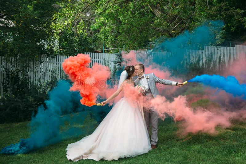 The bride and groom with smoke bombs on a field with green grass. Newlyweds walking outdoors at wedding day. Girl in. Luxury long white dress and men in stock photo