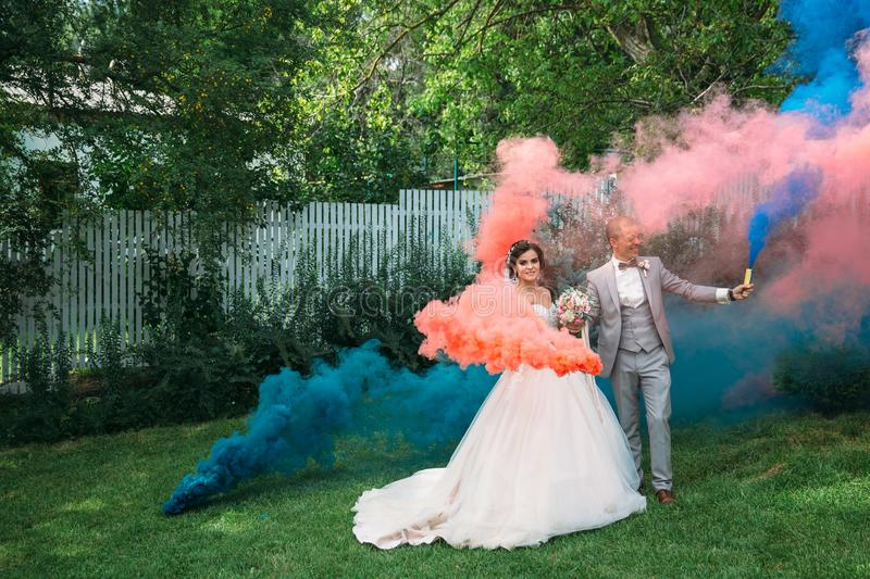 The bride and groom with smoke bombs on a field with green grass. Newlyweds walking outdoors at wedding day. Girl in. Luxury long white dress and men in stock image