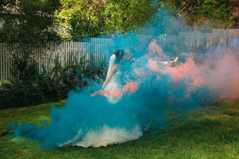 The bride and groom with smoke bombs on a field with green grass. Newlyweds walking outdoors at wedding day. Girl in. Luxury long white dress and men in stock photos