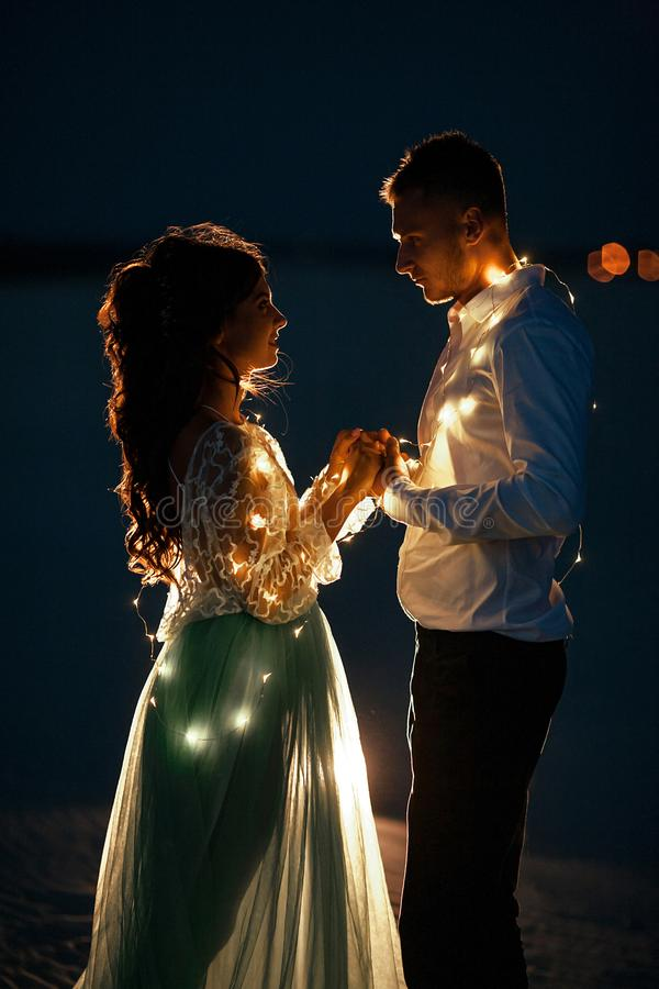 Bride and groom stand and hold hands next to garland of light bulbs at night. Closeup. Bride and groom stand, hold hands and look at each other next to garland royalty free stock photography