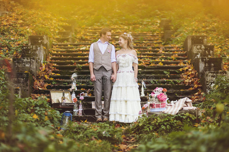 The bride and groom stand near the stone steps surrounded by wedding decor royalty free stock photography