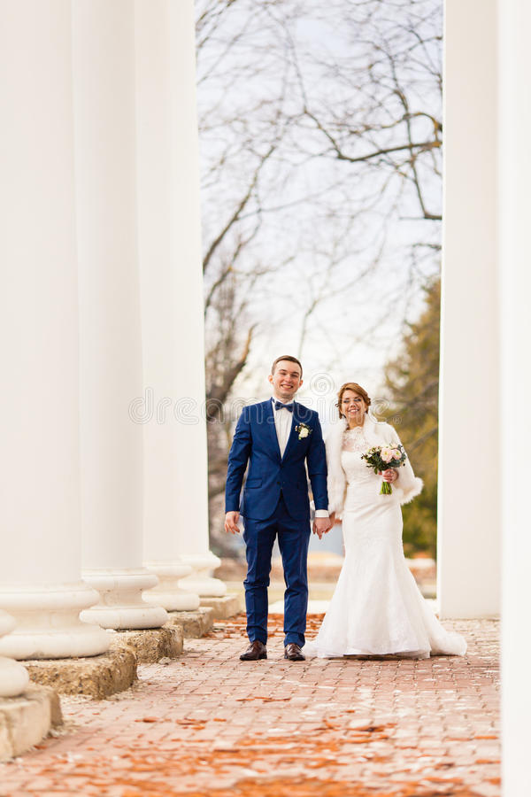 The bride and groom are standing between the columns royalty free stock photos