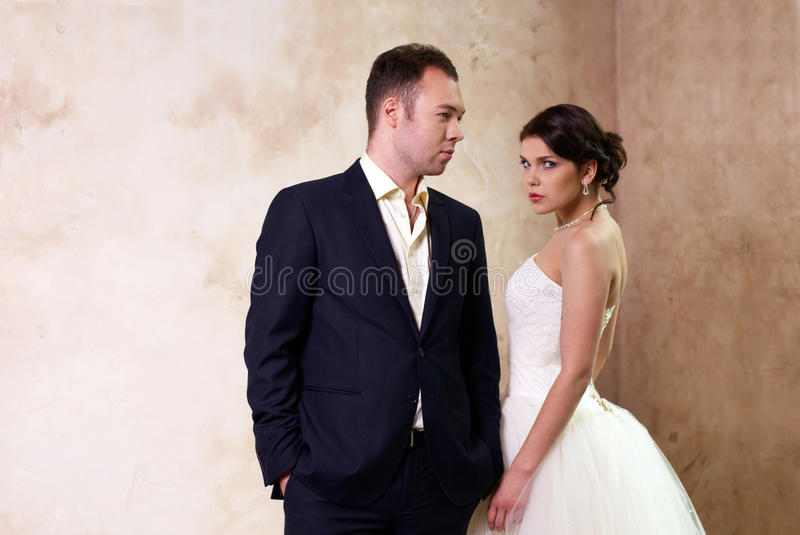 Bride and groom standing in empty room stock images
