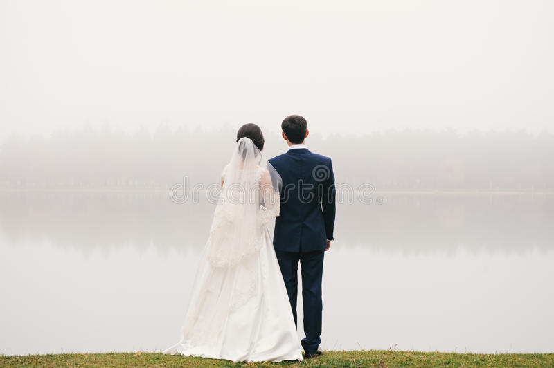 Bride and groom standing in front of lake looking far. Bride and groom standing in front of the lake and looking into the distance in the direction of the park stock photo
