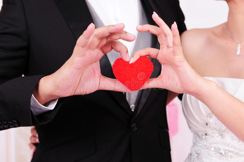 Bride and groom standing together with heart stock photo