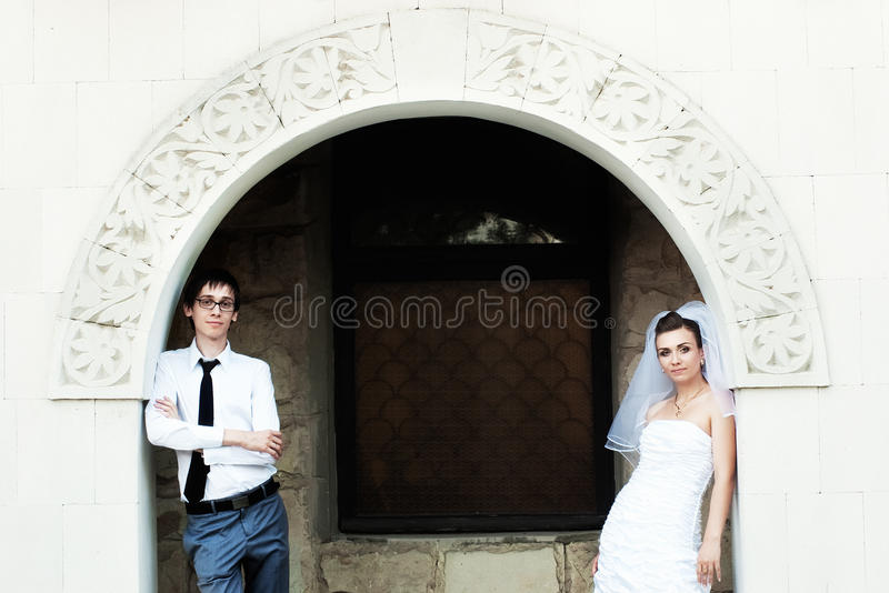 Download Bride And Groom Standing Under White Arch Stock Photo - Image: 10097012