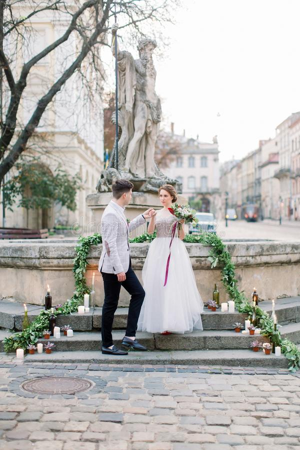 Bride and groom on the stone monument stairs, wedding walk in old city. Wedding ceremony, decorated with candles stock image