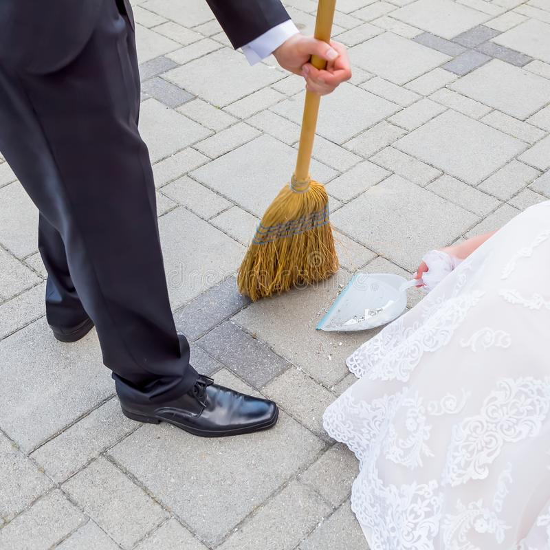 Bride and groom sweeping the pieces of happiness on wedding. royalty free stock images