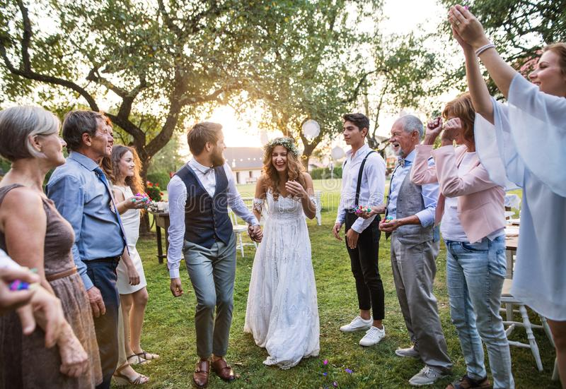 Bride, groom and guests at wedding reception outside in the backyard. stock images