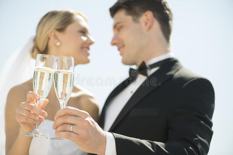 Bride And Groom Toasting Champagne Flutes Against Sky. Low angle view of young bride and groom toasting champagne flutes against sky stock images