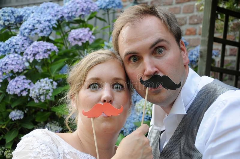 Bride and groom pose giggly in front of a photo-booth. Bride and groom with toy moustaches posing in front of a photo-booth. They feel very silly royalty free stock images
