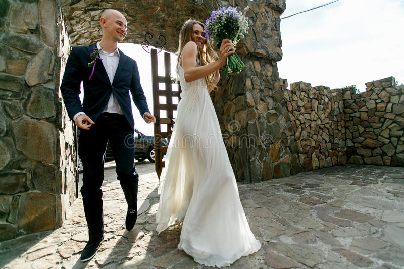 Bride and groom walk dancing into the stone courtyard royalty free stock image