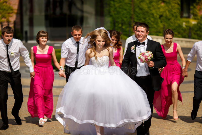 Bride and groom walk in the park being followed by their friends.  royalty free stock photography