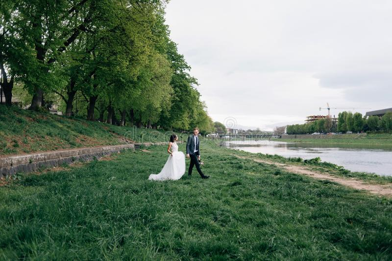 The bride and groom walk on the street. River bank, fresh air royalty free stock images
