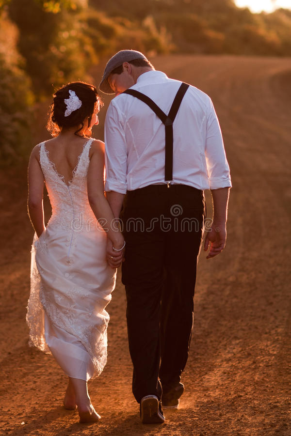 Bride and groom walking. At sunset