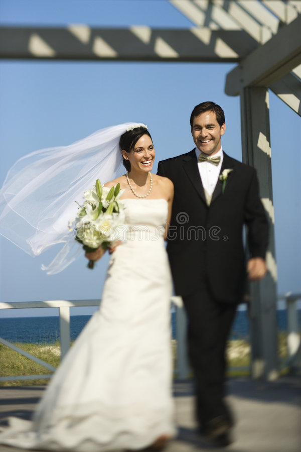 Bride and groom walking. Caucasian mid-adult bride and groom walking together smiling