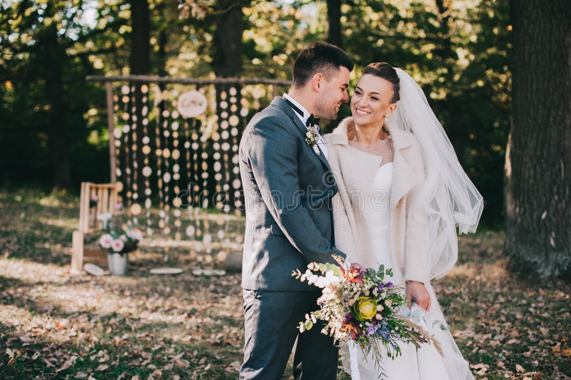 Bride and groom walking in the autumn forest stock photography