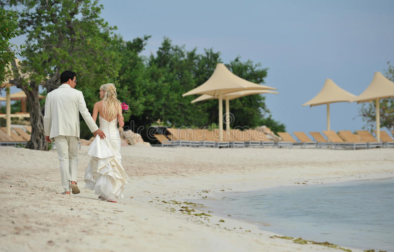 Bride and groom walking on caribbean beach royalty free stock photo