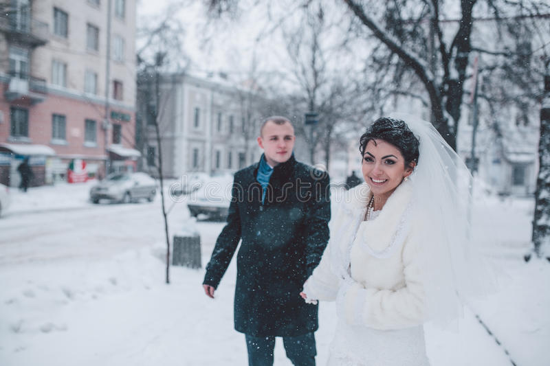 Bride and groom walking on the city royalty free stock photos