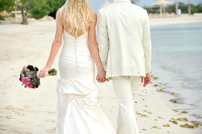 Bride and groom walking hand in hand stock image