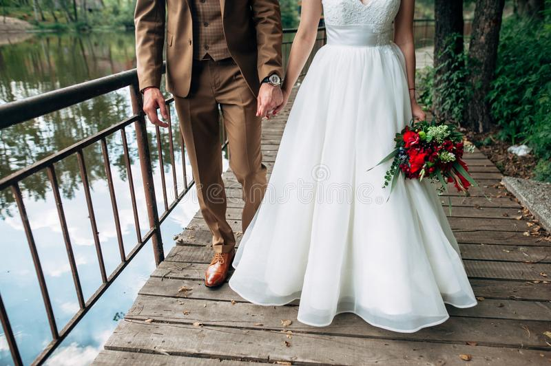 Bride and groom are walking and holding hands stock photo