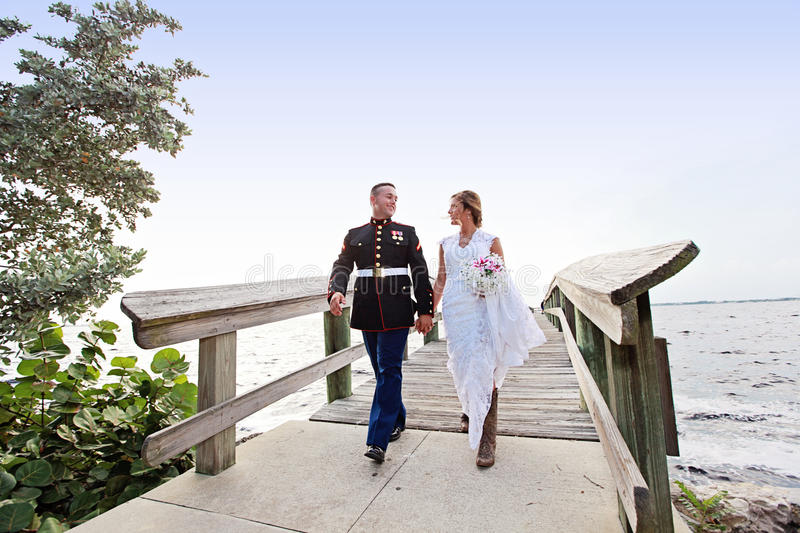 Bride and Groom walking. A bride and military groom holding hands walking on a boardwalk outdoors stock photos
