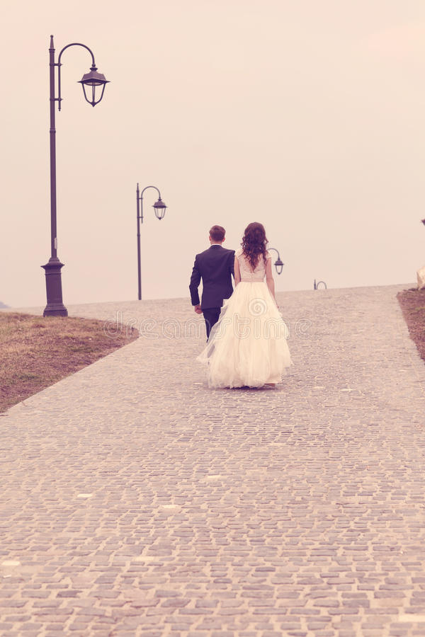 Bride and groom walking on pavement royalty free stock image