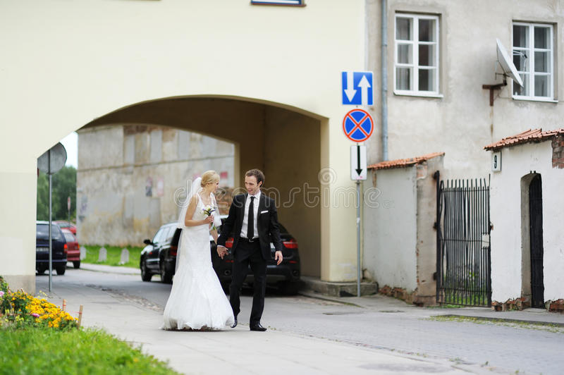 Bride And Groom Walking In A Town Stock Photo