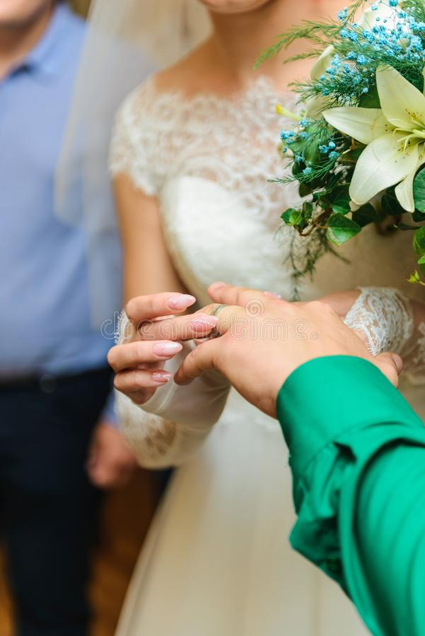 Bride and groom wearing wedding rings. Vertical frame royalty free stock image