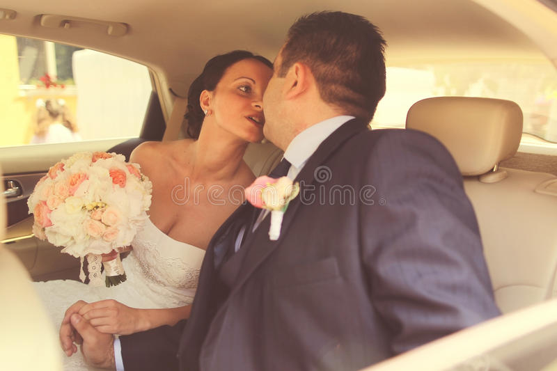 Bride and groom in wedding car royalty free stock image