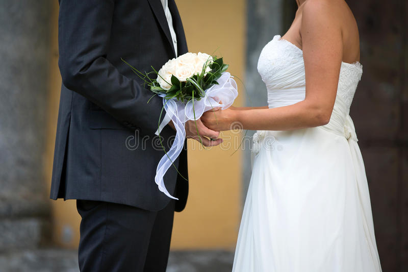 Bride and Groom in a wedding day. Bride and Groom Holding Hands Outdoors in a Wedding Day stock photo