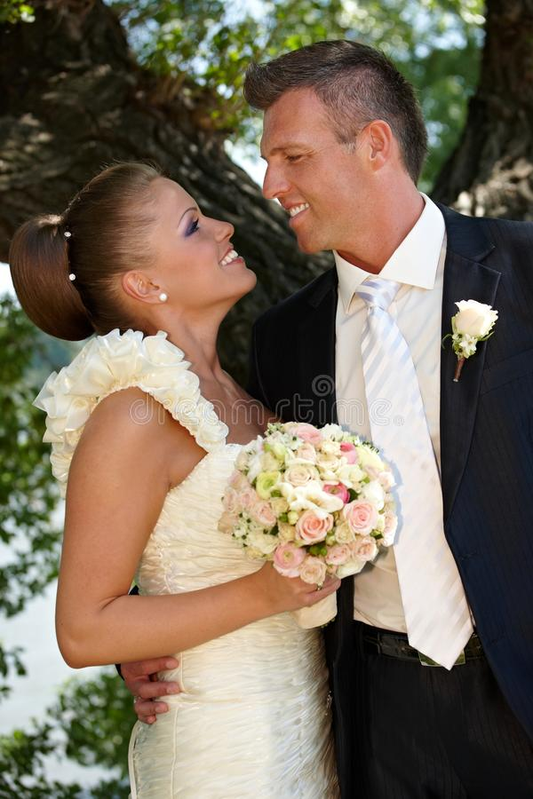 Bride and groom on wedding-day. Bride and groom kissing on wedding-day outdoors. Side view royalty free stock photos