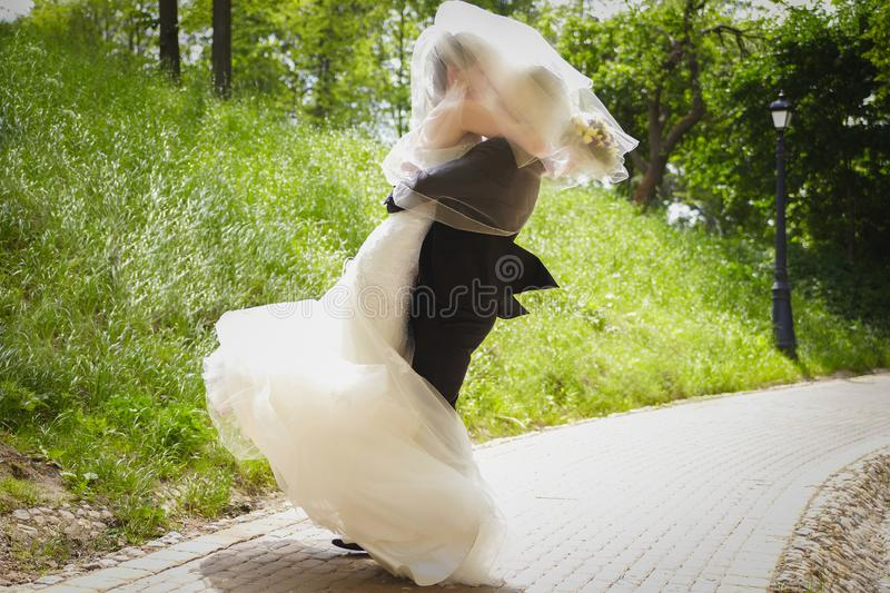 The bride and groom in the summer on a Sunny day spinning in the dance royalty free stock image