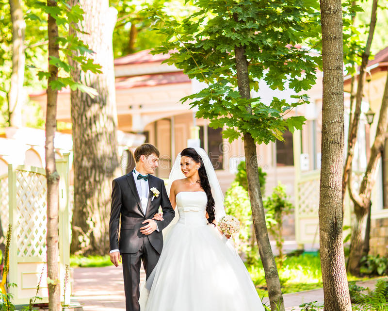 Bride and Groom at wedding Day walking Outdoors on spring nature. Bridal couple, Happy Newlywed woman and man embracing stock photos