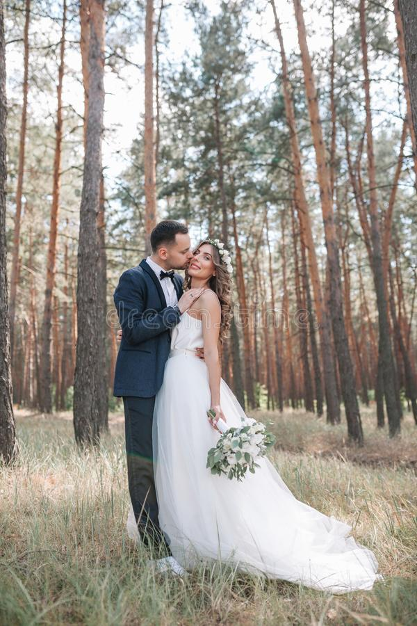 Bride and groom at wedding Day walking Outdoors on summer nature. Bridal couple, Happy Newlywed woman and man embracing in green stock image