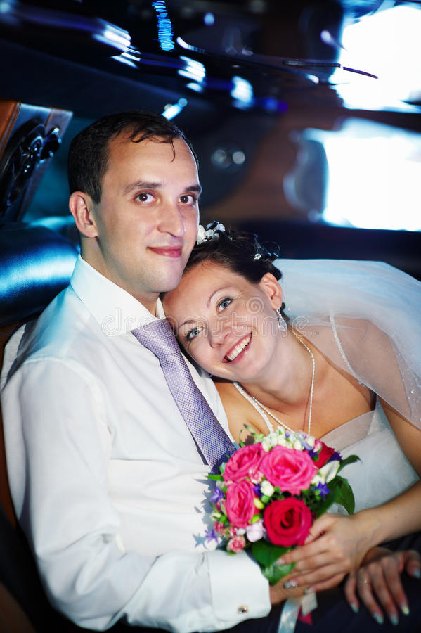The bride and groom in a wedding limo